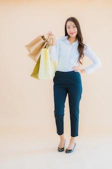 Portret pięknej młodej azjatyckiej kobiety biznesu z dużą ilością torby na zakupy z handlu detalicznego i domu towarowego