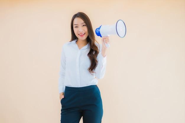 Portret pięknej młodej azjatyckiej kobiety biznesu z megafonem do cummunication