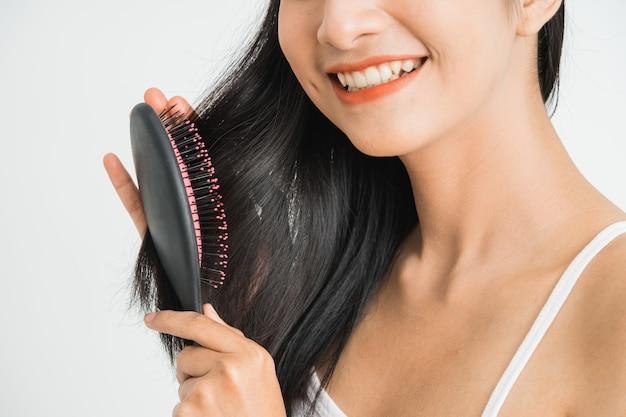 Portret pięknej młodej azjatyckiej kobiety - czesanie jej długie proste włosy