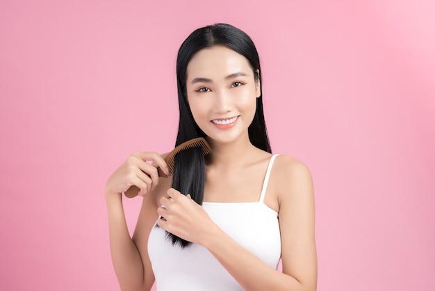 Portret pięknej młodej azjatyckiej kobiety czeszącej włosy, patrzącej na kamerę i uśmiechającej się