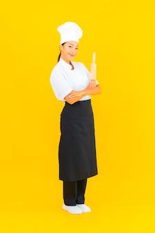Portret pięknej młodej azjatyckiej kobiety kucharz z wałkiem do ciasta na żółtym tle na białym tle