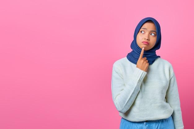 Portret pięknej młodej azjatyckiej kobiety myślącej o pytaniu z ręką na podbródku