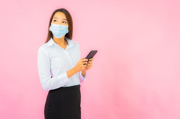 Portret pięknej młodej azjatyckiej kobiety nosić maskę do ochrony przed covid19 i koronawirusem na różowej ścianie
