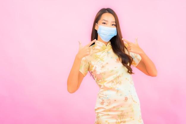 Portret pięknej młodej azjatyckiej kobiety noszącej maskę do ochrony przed covid19 i koronawirusem