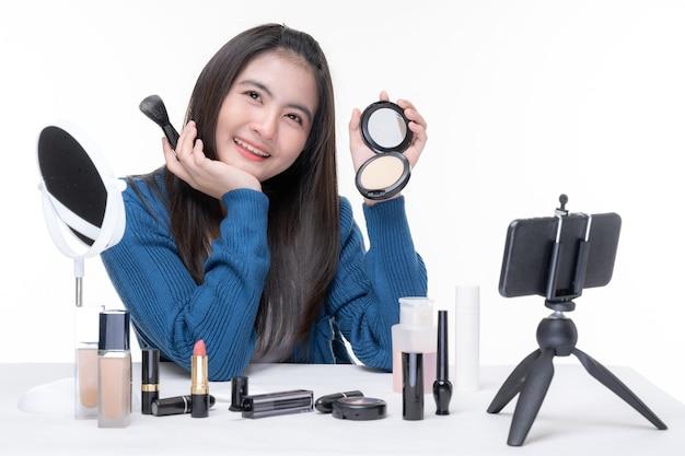 Portret pięknej młodej azjatyckiej kobiety piękna vlogger robi makijaż patrząc w kamerę nagrywanie i przesyłanie strumieniowe wideo do udostępniania w mediach społecznościowych