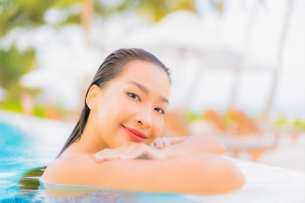 Portret pięknej młodej azjatyckiej kobiety relaksujący wypoczynek przy odkrytym basenie z plażą oceanu morskiego