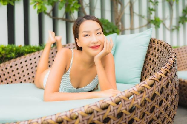 Portret pięknej młodej azjatyckiej kobiety relaksujący wypoczynek wokół odkrytego basenu w hotelowym kurorcie na wakacje w podróży