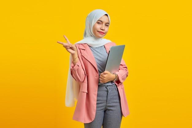 Portret pięknej młodej azjatyckiej kobiety trzymającej laptopa i robiącej znak pokoju palcami odizolowanymi na żółtym tle