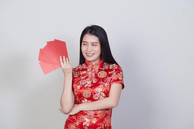 Portret pięknej młodej azjatyckiej kobiety ubrana w chińską sukienkę z czerwonym pakietem prezent pieniężny gratulacyjny powitanie szczęśliwego nowego roku 2021 odizolowany na jasnoszarym tle z miejscem na kopię