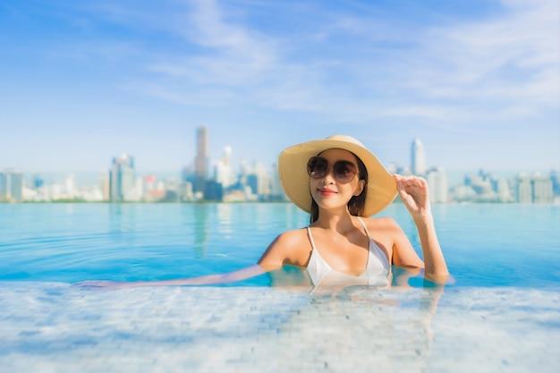 Portret pięknej młodej azjatyckiej kobiety uśmiech relaksujący wypoczynek wokół odkrytego basenu z widokiem na miasto