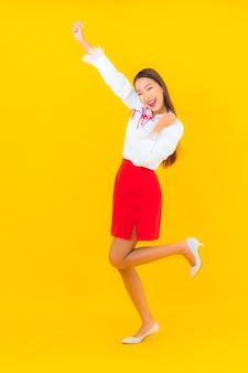 Portret pięknej młodej azjatyckiej kobiety uśmiech w akcji na żółto