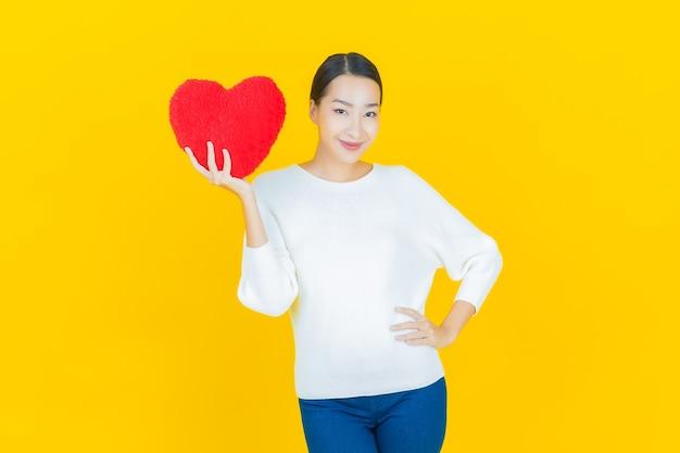 Portret pięknej młodej azjatyckiej kobiety uśmiech w kształcie poduszki w kształcie serca na żółto
