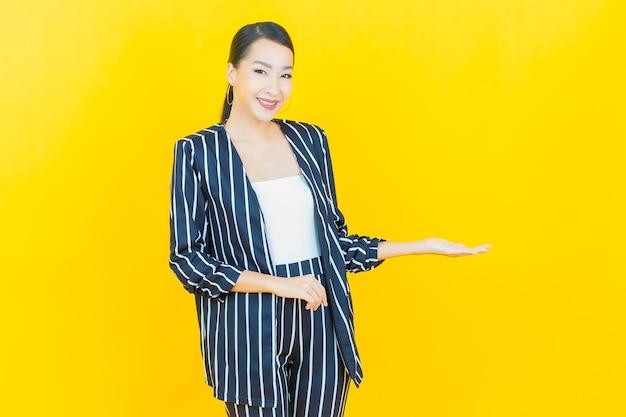 Portret pięknej młodej azjatyckiej kobiety uśmiech z akcją na kolorowym tle