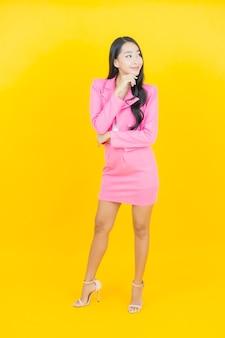 Portret pięknej młodej azjatyckiej kobiety uśmiech z akcją na ścianie w kolorze żółtym