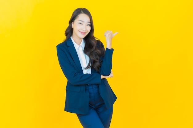 Portret pięknej młodej azjatyckiej kobiety uśmiech z akcją na żółto