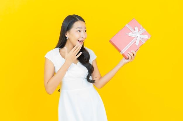 Portret pięknej młodej azjatyckiej kobiety uśmiech z czerwonym pudełkiem na prezent