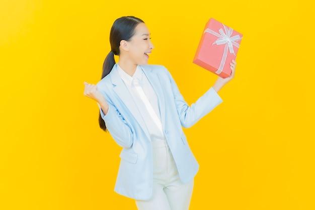 Portret pięknej młodej azjatyckiej kobiety uśmiech z czerwonym pudełkiem na żółto