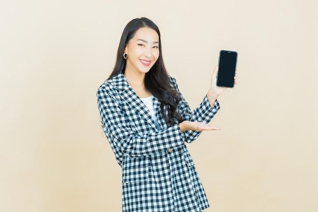 Portret pięknej młodej azjatyckiej kobiety uśmiech z inteligentnym telefonem komórkowym na beżowym