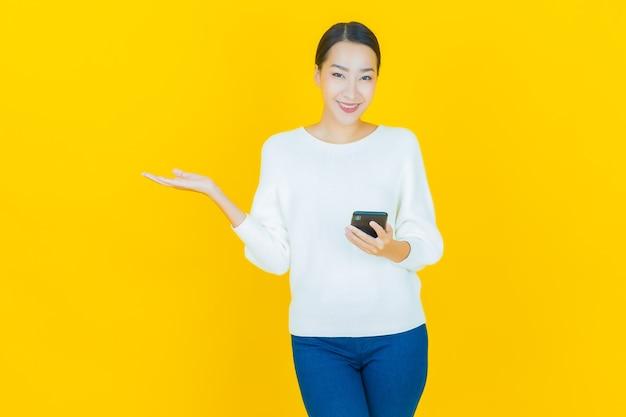 Portret pięknej młodej azjatyckiej kobiety uśmiech z inteligentnym telefonem komórkowym na żółto