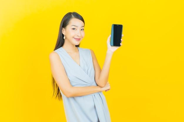 Portret pięknej młodej azjatyckiej kobiety uśmiech z inteligentnym telefonem komórkowym