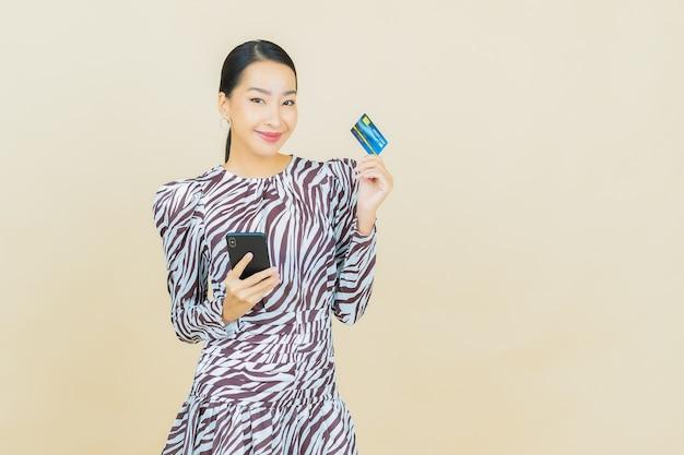 Portret pięknej młodej azjatyckiej kobiety uśmiech z kartą kredytową na beżowym