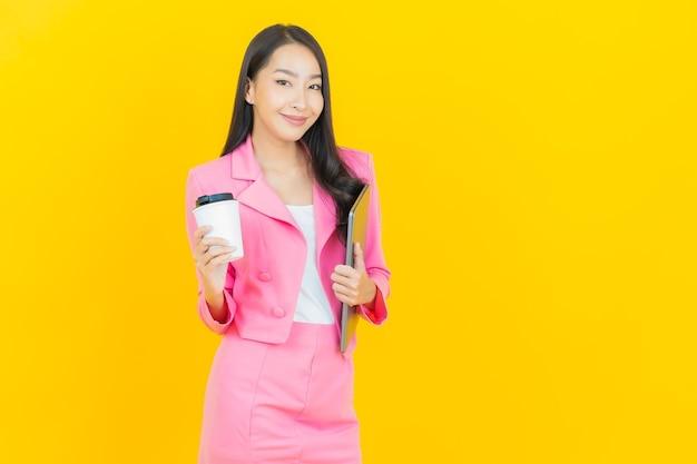 Portret pięknej młodej azjatyckiej kobiety uśmiech z laptopem na żółtej izolowanej ścianie