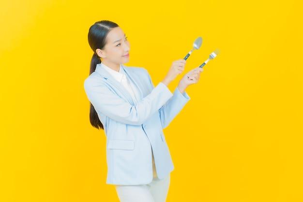 Portret pięknej młodej azjatyckiej kobiety uśmiech z łyżką i widelcem na żółto