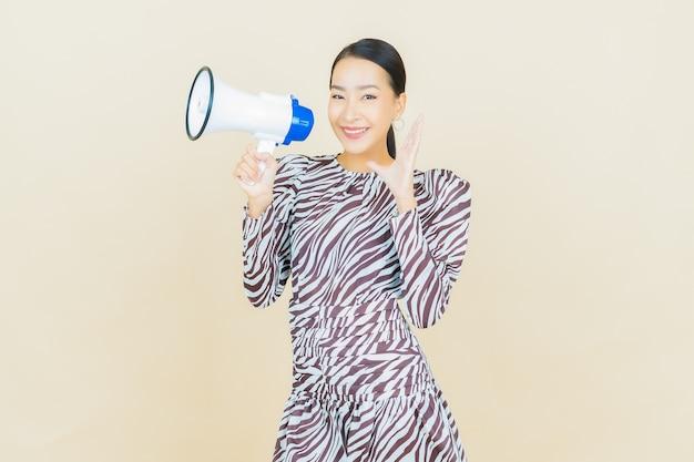 Portret pięknej młodej azjatyckiej kobiety uśmiech z megafonem na beżu