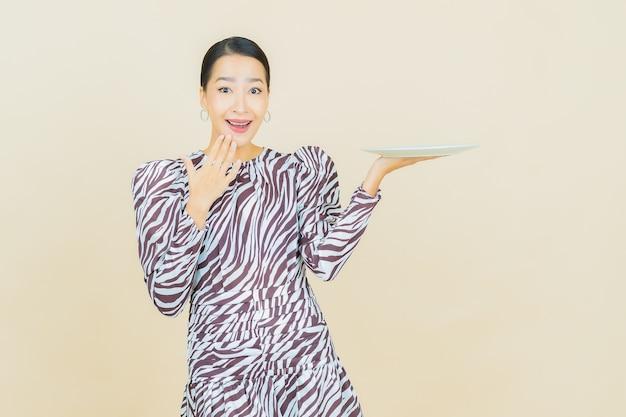 Portret pięknej młodej azjatyckiej kobiety uśmiech z pustym talerzem na beżowym talerzu