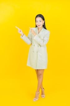 Portret pięknej młodej azjatyckiej kobiety uśmiecha się i wskazuje w lewo na kolorowej ścianie