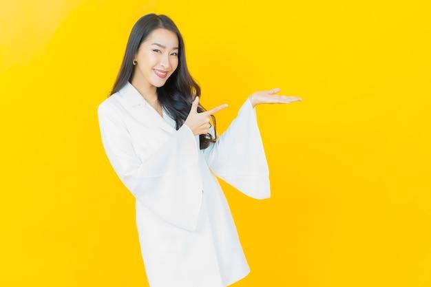 Portret pięknej młodej azjatyckiej kobiety uśmiecha się na żółtej ścianie