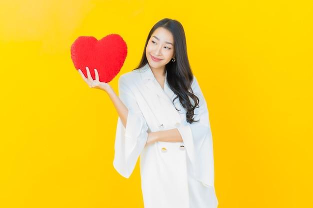 Portret pięknej młodej azjatyckiej kobiety uśmiecha się w kształcie poduszki w kształcie serca na żółtej ścianie