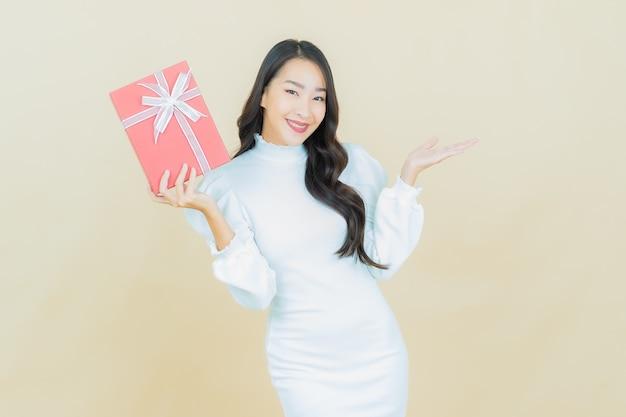 Portret pięknej młodej azjatyckiej kobiety uśmiecha się z czerwonym pudełkiem na kolorowej ścianie