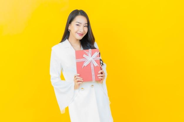Portret pięknej młodej azjatyckiej kobiety uśmiecha się z czerwonym pudełkiem na żółtej ścianie
