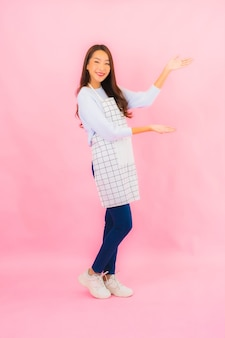 Portret pięknej młodej azjatyckiej kobiety w kuchni nosić fartuch na różowej ścianie na białym tle