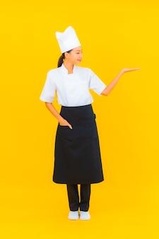Portret pięknej młodej azjatyckiej kobiety w mundurze szefa kuchni lub kucharza z kapeluszem na żółtym tle na białym tle