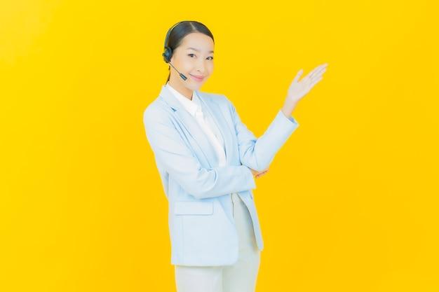 Portret pięknej młodej azjatyckiej kobiety z call center centrum obsługi klienta na żółto
