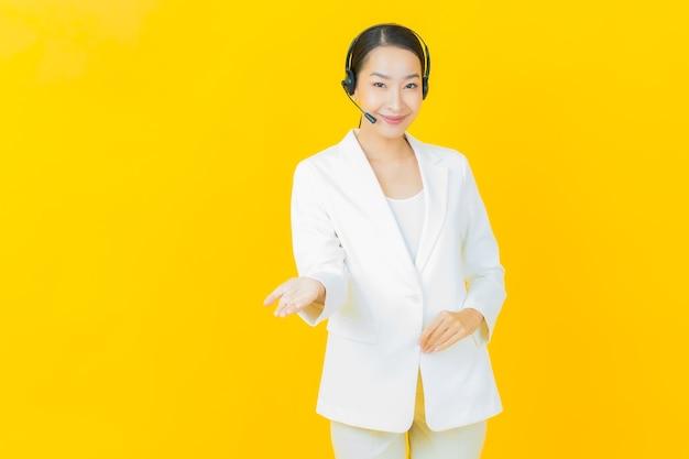 Portret pięknej młodej azjatyckiej kobiety z centrum obsługi klienta call center na żółtej ścianie