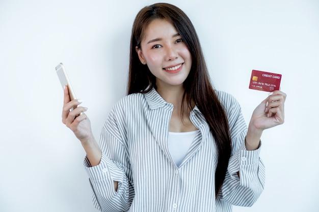 Portret pięknej młodej azjatyckiej kobiety z długimi włosami, trzymającej czerwoną kartę kredytową i smartfona, jej oczy błyszczą w aparacie