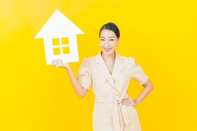 Portret pięknej młodej azjatyckiej kobiety z domowym lub domowym znakiem papieru na kolorowej ścianie
