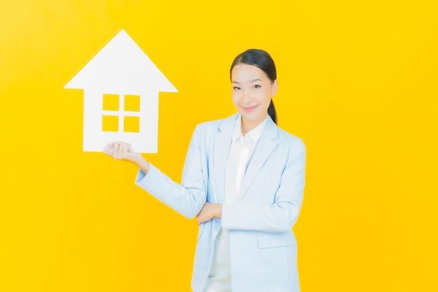 Portret pięknej młodej azjatyckiej kobiety z domowym lub domowym znakiem papieru na żółto