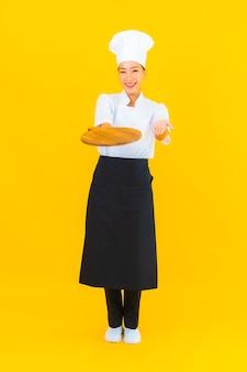 Portret pięknej młodej azjatyckiej kobiety z drewnianą deską do krojenia na żółtym tle na białym tle