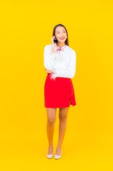 Portret pięknej młodej azjatyckiej kobiety z inteligentnym telefonem komórkowym na żółto
