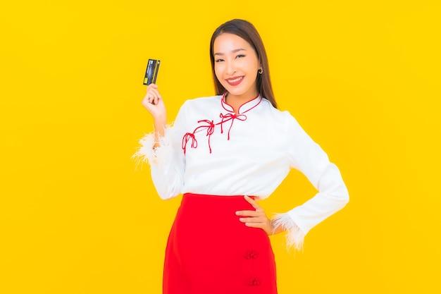 Portret pięknej młodej azjatyckiej kobiety z kartą kredytową na zakupy online na żółto