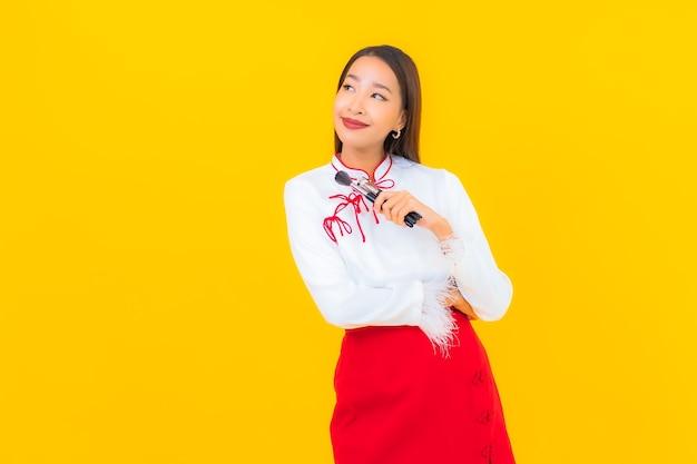Portret pięknej młodej azjatyckiej kobiety z kosmetycznym pędzlem do makijażu na żółto