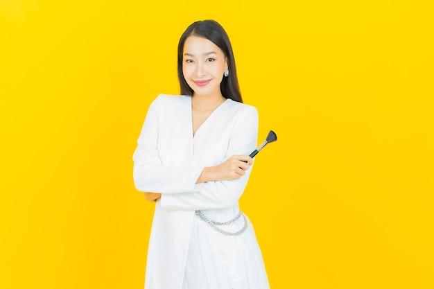Portret pięknej młodej azjatyckiej kobiety z kosmetycznym pędzlem do makijażu