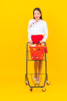 Portret pięknej młodej azjatyckiej kobiety z koszem spożywczym z supermarketu na żółtym
