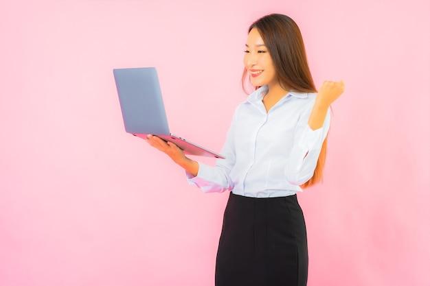 Portret pięknej młodej azjatyckiej kobiety z laptopem na różowej ścianie