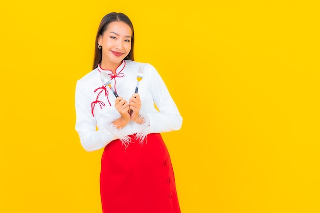 Portret pięknej młodej azjatyckiej kobiety z łyżką i widelcem na żółto