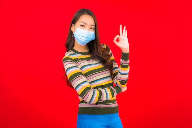 Portret pięknej młodej azjatyckiej kobiety z maską do ochrony covid19